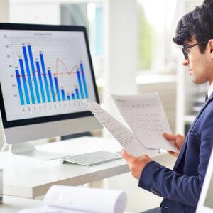 homem analisando relatório em um monitor