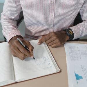Homem fazendo anotações em um caderno