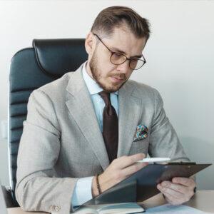 Homem analisando cálculos em uma prancheta