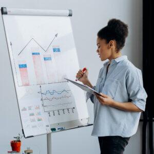 Mulher analisando gráficos em um quadro.